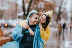 De gelukkige paar het houden van kerel en zijn meisje gekleed in regenjassen koesteren op de straat in de regen stock fotografie
