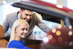 De gelukkige paar het kopen auto in auto toont of salon Royalty-vrije Stock Fotografie