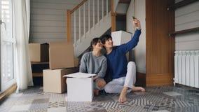 De gelukkige de paarman en vrouw maken online videogesprek met smartphone na verhuizing Zij begroeten vrienden stock video