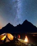 De gelukkige paarwandelaars die face to face vooraan tent dichtbij kampvuur zitten glanst onder sterrige hemel bij nacht royalty-vrije stock foto