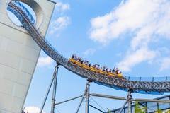 De gelukkige parkbezoekers genieten van hun achtbaanrit bij Dom van Tokyo Royalty-vrije Stock Afbeeldingen