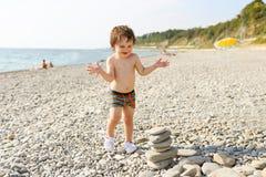 De gelukkige peuter toren van de bouwkiezelstenen op het strand Royalty-vrije Stock Foto