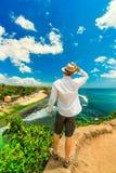 De gelukkige reismens die met hoed de zomer van vakantie op tropisch eiland Bali genieten en geniet van verbazend het hoogste str stock fotografie