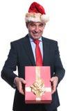 De gelukkige rijpe bedrijfsmens met santahoed geeft u a presen Stock Fotografie