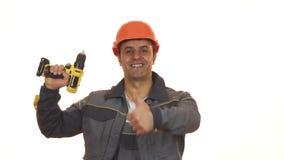 De gelukkige rijpe de industriearbeider in bouwvakker het tonen beduimelt het tegenhouden van boor royalty-vrije stock afbeelding