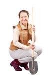 De gelukkige rijpe vrouw zit met spade Royalty-vrije Stock Afbeelding