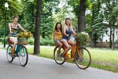 De gelukkige rit van boho elegante meisjes samen op fietsen in park Stock Afbeeldingen