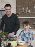 De gelukkige Salade van Vaderand son preparing bij Keukenteller Stock Foto's