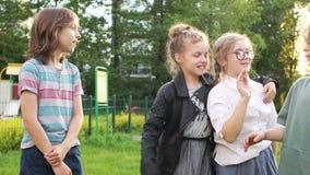 De gelukkige schoolkinderenklasgenoten begroeten elkaar Terug naar school, lopen de kinderen in het park in de avond, de dag van stock videobeelden