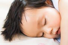 De gelukkige slaap van het babymeisje op het bed Stock Foto's
