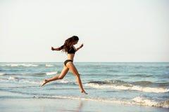 De gelukkige slanke dame stelt op zee strand in werking stock foto's