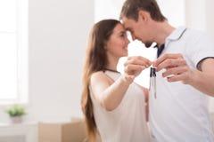 De gelukkige sleutels van de paarholding van hun nieuw huis Royalty-vrije Stock Afbeeldingen
