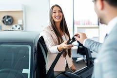 De gelukkige sleutels van de vrouwenholding tot haar nieuwe auto bij het handel drijven stock fotografie