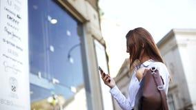 De gelukkige slimme onderneemster loopt op de straat en maakt beelden door haar celtelefoon stock video