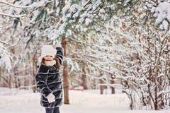 De gelukkige spelen van het kindmeisje met sneeuw op pijnboomboom in de winterbos Royalty-vrije Stock Fotografie