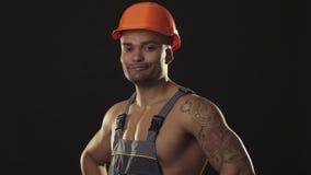 De gelukkige spier Afrikaanse mannelijke bouwer in bouwvakker het glimlachen het tonen beduimelt omhoog stock fotografie