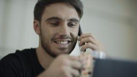 De gelukkige sprekende telefoon van het mensengezicht De gelukkige telefoon van de zakenmanvraag en het drinken thee stock video