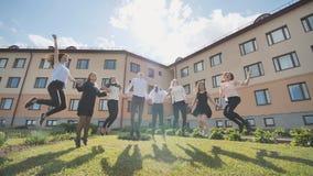 De gelukkige sprong van schooljongensgediplomeerden op de achtergrond van hun school stock fotografie