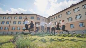 De gelukkige sprong van schooljongensgediplomeerden op de achtergrond van hun school royalty-vrije stock foto's