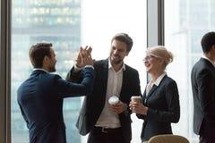 De gelukkige stafmedewerkers geven hoogte vijf tijdens vriendschappelijke bespreking in bureau stock foto's
