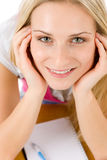 De gelukkige studentenvrouw schrijft thuiswerk bij lijst Stock Foto
