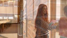 De gelukkige studentes gaan in de school binnen stock footage