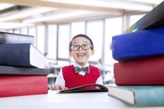 De gelukkige studie van de nerdjongen bij bibliotheek Stock Afbeeldingen
