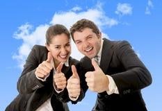 De gelukkige succesvolle bedrijfs Spaanse vrouw en het Kaukasische man dragen passen het geven van duimen aan omhoog glimlachend  Royalty-vrije Stock Foto