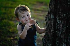 De gelukkige tarwe van de Jongensholding in zijn mond met overall  stock foto's