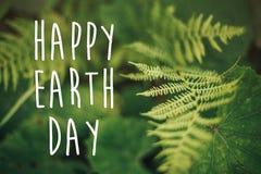 De gelukkige tekst van de aardedag, concept mooi varenblad en mos binnen stock fotografie