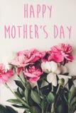 De gelukkige tekst van de moeder` s dag op roze pioenenboeket op rustiek wit royalty-vrije stock foto