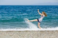 De gelukkige tiener geniet van vakantie schoppend het water bij het strand van Sicilië stock afbeelding