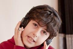 De gelukkige tiener met Steunen en luistert Muziek Stock Foto's