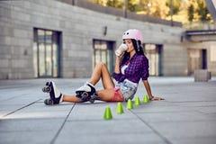 De gelukkige tiener rollerblading zitting op straat en drinkt koffie Royalty-vrije Stock Foto's