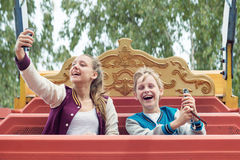 De gelukkige Tienerjarenrit op de carrousel en maakt selfie Royalty-vrije Stock Foto