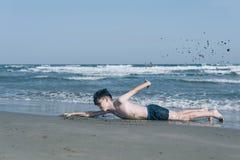De gelukkige tienerjongen die pret opleiding hebben of imiteert het zwemmen van op het zand Ð ¾ n het strand stock afbeeldingen
