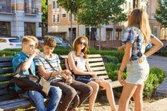 De gelukkige 4 tienervrienden of de middelbare schoolstudenten hebben pret, spreken, die telefoon in stad op bank lezen Vriendsch stock foto's