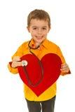 De gelukkige toekomstige arts onderzoekt hart Royalty-vrije Stock Fotografie