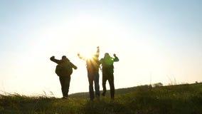 De gelukkige toeristen met rugzakken stellen en golven hun handen in werking Groepswerk van bedrijfsmensen het commerciële team m stock videobeelden