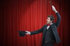 De gelukkige tovenaar of de illusionist tonen magische truc Rode gordijnen op achtergrond Royalty-vrije Stock Afbeelding