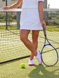 De gelukkige tribunes van het sportenmeisje met racket op hof bij zonnige de zomerdag Royalty-vrije Stock Afbeeldingen