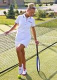 De gelukkige tribunes van het sportenmeisje met racket op hof bij zonnige de zomerdag Stock Afbeeldingen