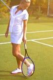 De gelukkige tribunes van het sportenmeisje met racket op hof bij zonnige de zomerdag Royalty-vrije Stock Afbeelding