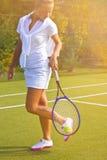 De gelukkige tribunes van het sportenmeisje met racket op hof bij zonnige de zomerdag Royalty-vrije Stock Foto's
