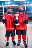 De gelukkige trofee van de het ijshockeywinnaar van jongensspelers stock foto
