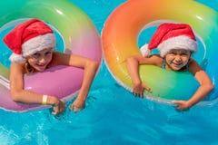 De gelukkige twee meisjes die in een blauwe pool in Kerstmanhoeden drijven op een blauwe achtergrond, bekijken de camera en de gl stock fotografie