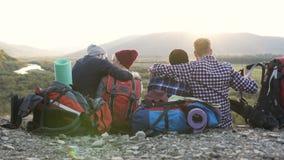 De gelukkige twee vrouwen die op de grond in de berg zitten terwijl komend hun vrienden, die en zitten samen koesteren stock videobeelden