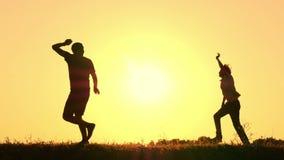 De gelukkige vader en zijn kinderen het spelen lopen rond bij zonsondergang in de zomer Silhouet van een gelukkige familie stock videobeelden