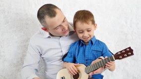 De gelukkige vader en de zoon spelen de gitaar en zingen Het voelen van de emoties van geluk, liefde, vreugde en glimlach stock videobeelden
