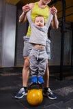 De gelukkige vader houdt de handen van zijn zoon die zich op kettlebells tegen bakstenen muur in de dwars geschikte gymnastiek be stock afbeelding